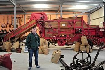 """L'Albert Rúbies davant d'una """"Ajuria Enea"""" al museu de Jaume Esteve, de maquinària agrícola antiga."""