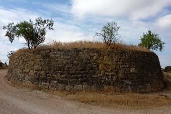 Una paret que tanca circularment un bancal elevat entre dos camins. El marge es conserva impecable en tota la   seva extensió.