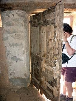 La porta de la cabana, amb triple forrellat de fusta. No sabem si és prou eficàs, però sí ben original.