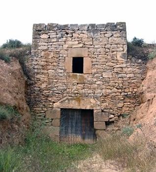 La façana, on es veu que la construcció està encaixada pels laterals. La part posterior també queda endinsada en el terreny i el de sobre és l'era, de grans dimensions.