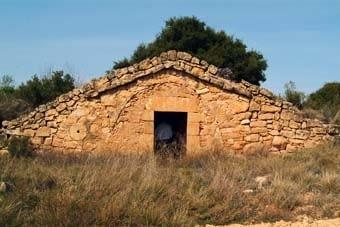 Un estil similar de cabana, que té un rodet integrat a la paret i un ràfec de llosetes bastant ben conservat.