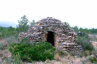B4.  Barraca en espiral.  L'exterior d'aquesta barraca s'ha fet en espiral, de manera que es pot pujar fins dalt i treure la pedra que  la  corona superiorment,  per tal de deixar pas al fum.