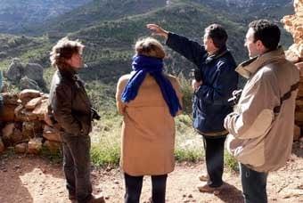 El guia explica com, des d'una masia propera, venien a  buscar pedra de la balma per bastir les seves parets.
