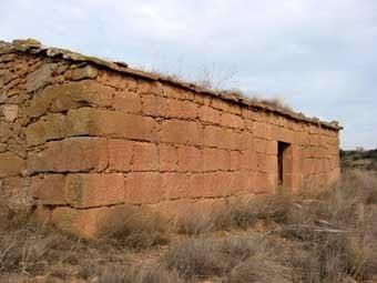 La darrera cabana d'aquesta visita és també grandiosa  i de gruixudes  parets de 1,80 m.  Està recolzada en la  paret oposada  a la façana,  i  té un arc de descàrrega  interior (s'observa a sota, sobre la llinda).