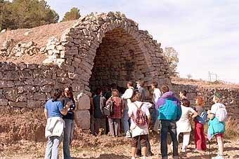 La seva alçada es posa en evidència amb aquest grup de visitants de la ruta del Cister.